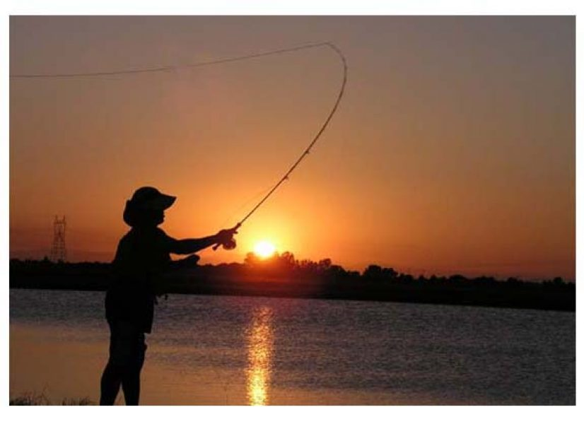 silhouette of person casting a line, fly fishing, at sunset